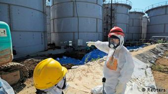 Japan's Economy, Trade and Industry Minister Toshimitsu Motegi (R), wearing a protective suit and a mask, inspects contaminated water tanks at the tsunami-crippled Fukushima Daiichi nuclear power plant in Fukushima prefecture August 26, 2013 (Photo: Reuters)
