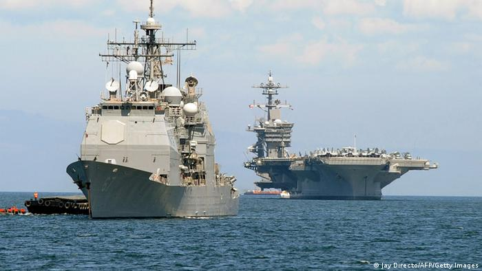 The US aircraft carrier Carl Vinson (R) and the cruiser USS Bunker Hill (L) (Photo credit should read JAY DIRECTO/AFP/Getty Images)