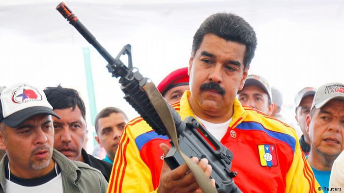 Presidente da Venezuela, Nicolás Maduro, segura fuzil durante destruição pública de armas confiscadas, em 2013