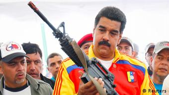 Venezuela's President Nicolas Maduro holds a weapon during a public destruction of confiscated weapons in Caracas August 8, 2013. (Photo: Carlos Garcia Rawlins / Reuters)