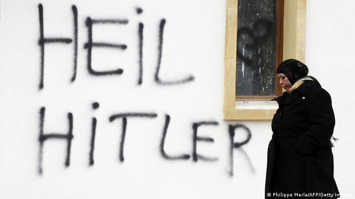 A woman walks past a wall with the writing Heil Hitler sprayed on it