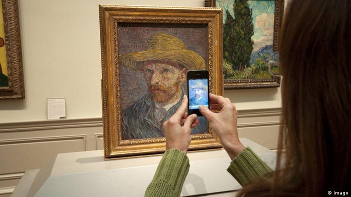 Frau macht mit einem Handy ein Foto von einem gemalten Selbstporträt (Foto: imago/CHROMORANGE)
