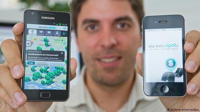 Werner Hoier vom Unternehmen «Streetspotr» in Nürnberg (Mittelfranken) hält zwei Smartphones mit der geöffneten Streetspotr-App nebeneinander (Foto vom 02.08.2012). Das Nürnberger Software-Unternehmen «Streetspotr» bietet bundesweit Mini-Jobs an, die User mit ihren Smartphones überall erledigen können. Sinn ist es unterwegs und nebenher Geld verdienen zu können. Eine Karte der App zeigt, wo die verschiedenen Minijobs - genannt Spots - liegen. Man kann dann dort fotografieren oder Informationen sammeln. Ist man vor Ort, kann man den Job annehmen und erledigen. Foto: Daniel Karmann dpa/lby