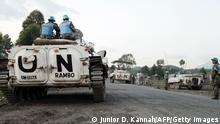 A child stands in front of Indian soldiers of the UN mission in the Democratic Republic of Congo (MONUSCO) driving an armoured vehicle at the border zone in Kagnaruchinya, 7 km north of Goma, on June 2, 2013. The M23 rebellion -- launched by Tutsi former soldiers who mutinied in April 2012 -- is the latest in years of violence that have ravaged the vast central African country's mineral-rich east. A peace deal signed in February by 11 regional countries had brought relative calm until it was broken in the three days leading up to Ban's visit. The two sides stopped fighting while the UN leader toured the flashpoint city of Goma. AFP PHOTO/Junior D. Kannah (Photo credit should read Junior D. Kannah/AFP/Getty Images) Erstellt am: 02 Jun 2013