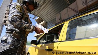 GettyImages 178139613 A member of the Iraqi interior ministry's security forces checks the ID of a cab driver at a checkpoint in Baghdad SABAH ARAR/AFP/Getty Images)