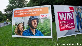 Two campaign signs shown side by side on a grassy corner Photo: Stefan Sauer/dpa