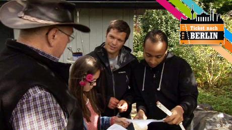 Drei Männer und eine Frau stehen in einem Kleingarten und schauen auf Papier.