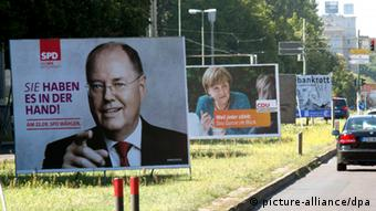In front, a poster showing Germany's SPD candidate Peer Steinbrück, and in the backround a poster of Angela Merkel. Foto: Jörg Carstensen dpa