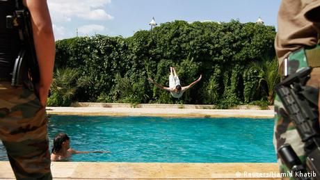 An opposition fighter jumps in an Aleppo swimming pool.