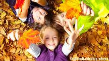 Kinder im Herbst Laub