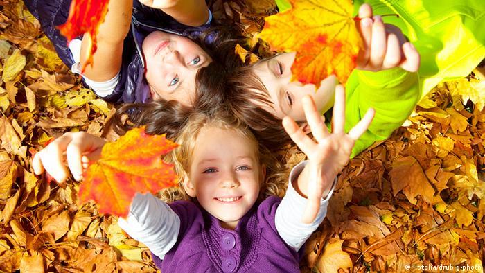Niños jugando con las hojas de otoño.
