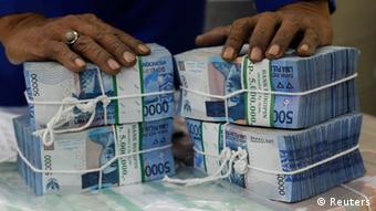 A worker prepares bundles of rupiah bank notes in Bank Mandiri in Jakarta in this July 9, 2013 file photo. Indonesia's annual inflation rate surged to 8.61 percent in July, the fastest pace in 4-1/2 years, due to much higher transport costs after fuel prices were hiked an average of 33 percent in late June, the statistics bureau said on August 1, 2013. REUTERS/Supri/Files (INDONESIA - Tags: BUSINESS) A general view shows a group of buildings seen from a street in Indonesia's capital city on June 29, 2012. The World Bank announced it was ready to provide Indonesia with a $2 billion loan, a backstop against any future financial shocks in one of Asia's fastest growing economies. AFP PHOTO / Bay ISMOYO (Photo credit should read BAY ISMOYO/AFP/Getty Images)