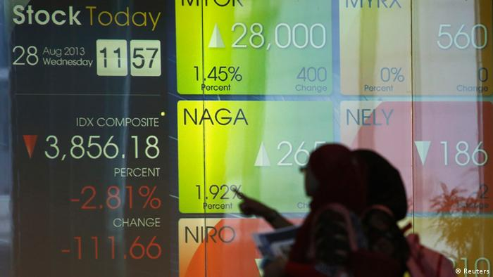Women walk in front of a screen in the Indonesia Stock Exchange (Photo: REUTERS/Beawiharta)
