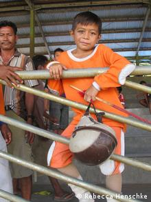 A young Indonesian boy wearing orange clothing supports himself on a beige metal gate while holding a brown-beige helmet. (Photo: Rebecca Henschke / DW)