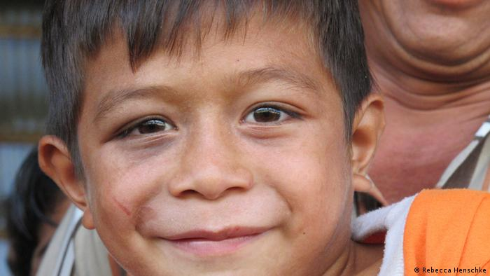 In a close-up of his face, a young Indonesian boy with dark hair and brown eyes smiles lopsidedly at the camera. (Photo: Rebecca Henschke / DW)