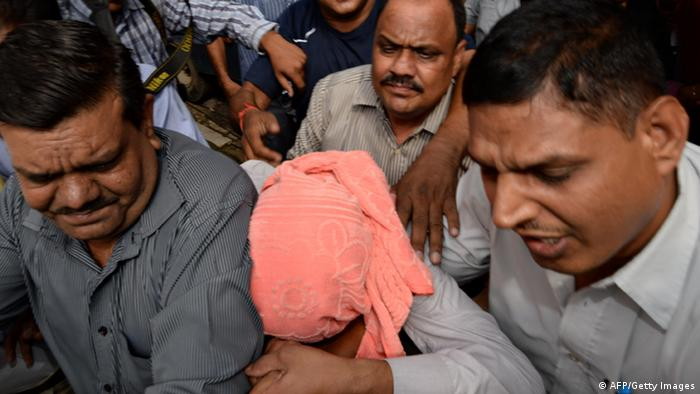 Indian policemen escort the juvenile (C, in pink hood), accused in the December 2012 gang-rape of a student, to a court in New Delhi on August 31, 2013. (Photo via AFP)