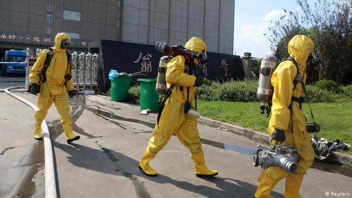 Rescuers in chemical protection suits walk outside a refrigeration unit of Shanghai Weng's Cold Storage Industrial Co. Ltd., in the Baoshan district of Shanghai August 31, 2013. A liquid ammonia leak from the refrigeration unit at the cold storage facility in Shanghai on Saturday has killed 15 people and injured 26 others, local authorities said. REUTERS/Stringer (CHINA - Tags: DISASTER ENVIRONMENT BUSINESS INDUSTRIAL) CHINA OUT. NO COMMERCIAL OR EDITORIAL SALES IN CHINA