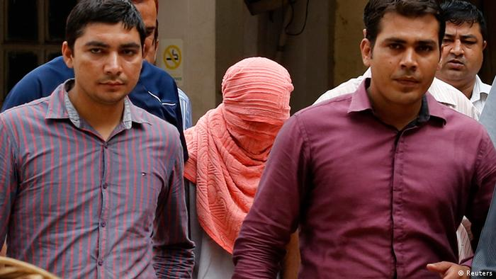 Plainclothes policemen escort an Indian teenager (head covered with towel) after he was sentenced at a juvenile court in New Delhi August 31, 2013. The Indian teenager was sentenced to three years in juvenile detention on Saturday for the December gang rape of a trainee physiotherapist, the first verdict in a case that sparked debate over whether India was too soft on young offenders. REUTERS/Anindito Mukherjee (INDIA - Tags: CRIME LAW TPX IMAGES OF THE DAY))