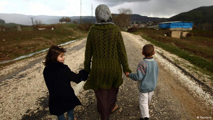 Syrian refugees walk down a dirt track