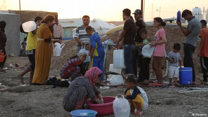 Syrian refugees, who fled the violence in Syria, use containers to collect water at the Arbat refugee camp in the northern Iraqi province of Sulaimaniya August 28, 2013. Picture taken August 28, 2013. REUTERS/Yahya Ahmad (IRAQ - Tags: SOCIETY POVERTY CIVIL UNREST CONFLICT IMMIGRATION)