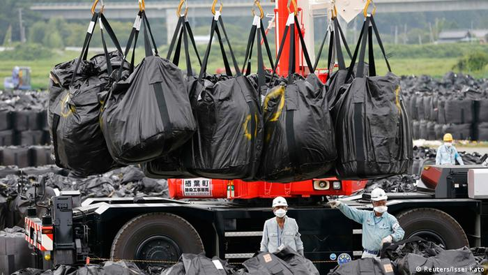 Workers move waste containing radiated soil, leaves and debris from the decontamination operation at a storage site