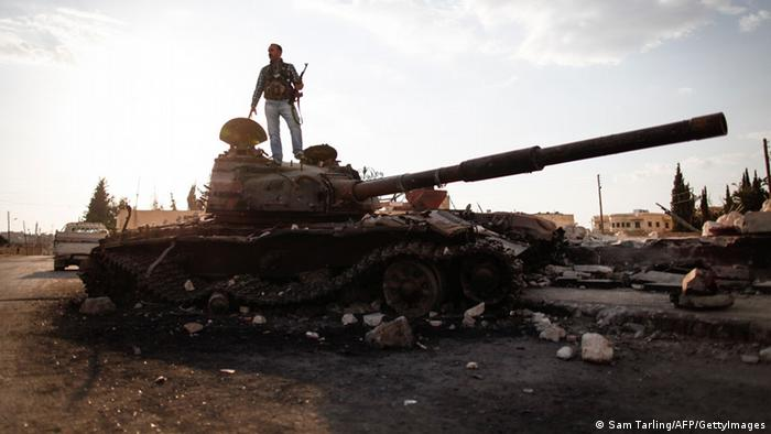 An armed fighter of the Free Syrian Army stands atop a destroyed Syrian army tank to have his picture taken by a passer-by in the northern Syrian town of Azaz, some 47km north of Aleppo, on September 10, 2012, as UN envoy Lakhdar Brahimi admitted he faced a 'very difficult' task in his bid to end the nearly 18-month conflict. AFP PHOTO/SAM TARLING (Photo credit should read SAM TARLING/AFP/GettyImages)