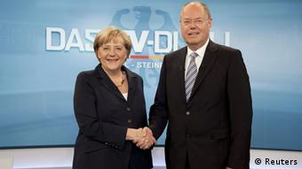 German Chancellor Angela Merkel shakes hands with her challenger, the top candidate in the upcoming German general elections of the Social Democratic Party (SPD), Peer Steinbrueck, during their TV duel in Berlin, September 1, 2013. German voters will take to the polls in a general election on September 22. REUTERS/ARD/Max Kohr/Pool (GERMANY - Tags: POLITICS ELECTIONS) FOR EDITORIAL USE ONLY. NOT FOR SALE FOR MARKETING OR ADVERTISING CAMPAIGNS. MANDATORY CREDIT. ATTENTION EDITORS: PICTURE TO BE USED ONLY IN RELATION TO THE TV DEBATE