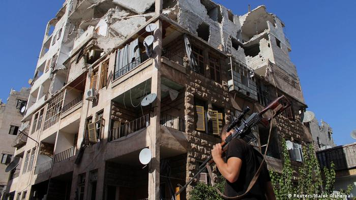 A Free Syrian Army fighter walks with his weapon in front of a damaged building in Aleppo's Al-Ezaa neighbourhood REUTERS/Malek Alshemali