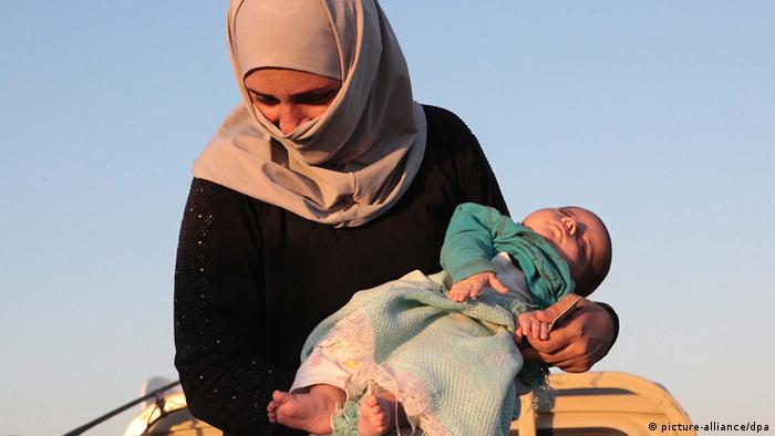 Syrian refugee woman fleeing violence in her country carrying her baby. EPA/STR +++(c) dpa - Bildfunk+++