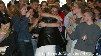 A winner gets a hug as other participants look on (c) Bundesgeschäftsstelle Jugend musiziert