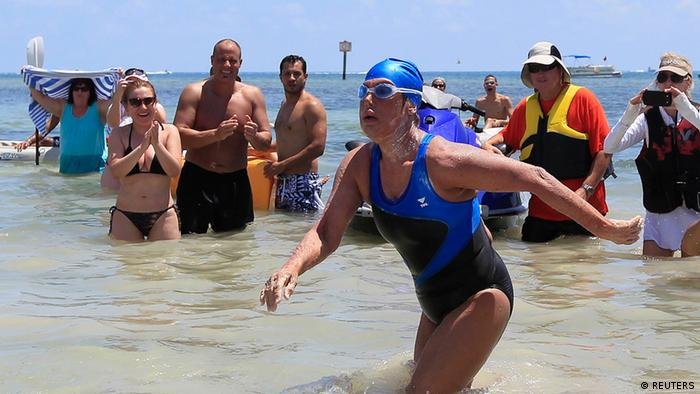 U.S. long-distance swimmer Diana Nyad , 64, walks to dry sand, completing her swim from Cuba as she arrives in Key West, Florida, September 2, 2013.REUTERS/Andrew Innerarity