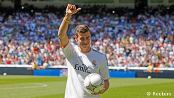 Gareth Bale of Wales gestures wearing his new Real Madrid club jersey at the Santiago Bernabeu stadium in Madrid, September 2, 2013. Thousands of Real Madrid fans flocked to the Bernabeu to welcome Bale on Monday after the nine-times European champions sealed the purchase of the Wales winger from Tottenham Hotspur for what the London club said was a world record fee. REUTERS/Paul Hanna (SPAIN - Tags: SPORT SOCCER)