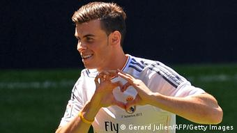 New Welsh striker of Real Madrid Gareth Bale makes a heart sign with his hands during his presentation at the Santiago Bernabeu stadium in Madrid on September 2, 2013. Bale was unveiled as a Real Madrid player today after his prolonged transfer from Tottenham Hotspur was finally completed for an unconfirmed world record fee late September 1. The Welshman has agreed a six-year deal believed to be worth 10 million euros net a year and will be presented to the media and the club's fans after undergoing a medical in the Spanish capital. AFP PHOTO/ GERARD JULIEN (Photo credit should read GERARD JULIEN/AFP/Getty Images)