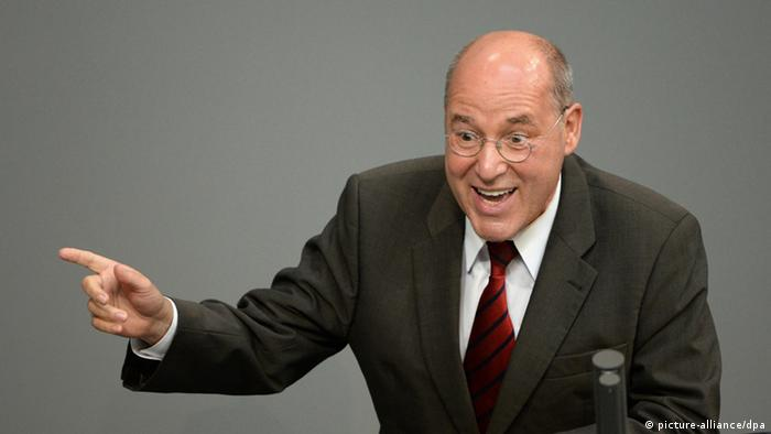 A balding older man wearing a business suit gestures with his finger to make a point while speaking publicly before a gray background. Photo: Soeren Stache