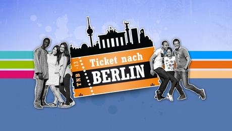 Die Teilnehmer und Teilnehmerinnen von Ticket nach Berlin stehen links und rechts vom Logo der Show
