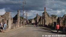 Pessoas caminhando numa rua ao lado de ruínas de casas