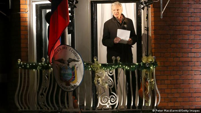 Julian Assange stands on a balcony of Ecuador's embassy at night (Photo by Peter Macdiarmid/Getty Images