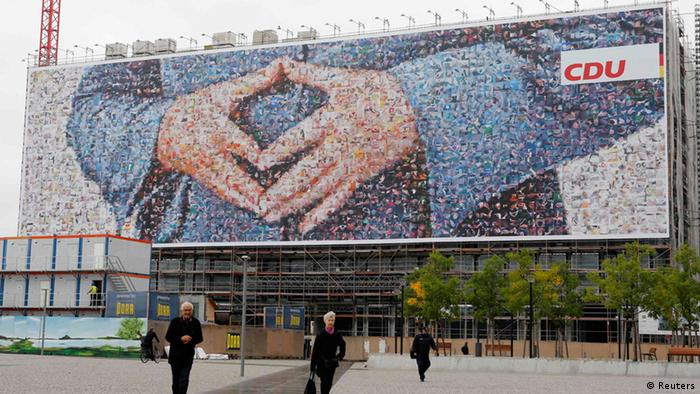 Pedestrians walk in front of a banner showing the hands of German Chancellor Angela Merkel, leader of Christian Democratic Union (CDU), composed of single photographs and installed on a facade of a construction site near Berlin's main train station September 2, 2013. REUTERS/Fabrizio Bensch (GERMANY - Tags: POLITICS ELECTIONS)