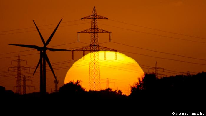 A sun setting behind wind turbines and electrcity masts (photo: Julian Stratenschulte/dpa)