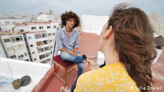 Young reporter conducting interview on a rooftop in Morocco