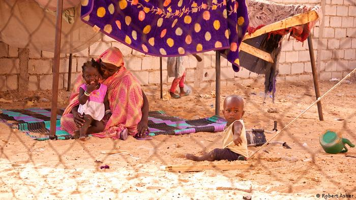 A woman sits on a dirt floor caring for a child