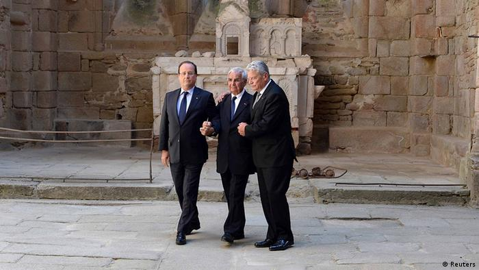 French President Francois Hollande (L), German President Joachim Gauck (R) and massacre survivor Robert Hebras hold hands as they stand in the church at Oradour-sur-Glane. PHOTO: Reuters/Jean-Pierre Muller