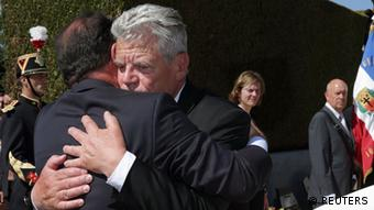 French President Francois Hollande (L) and German President Joachim Gauck hug after a ceremony at Oradour-sur-Glane, September 4, 2013.