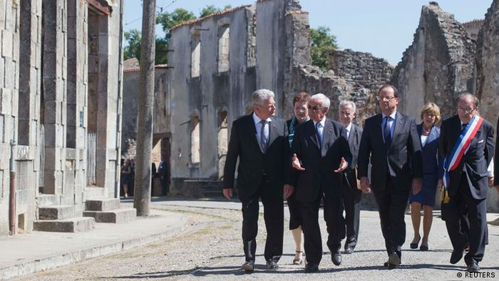 French President Francois Hollande (2ndR), German President Joachim Gauck (L), massacre survivor Robert Hebras (2ndL) and Mayor of Oradour-sur-Glane, Raymond Fugier, walk in the streets of the French martyr village of Oradour-sur-Glane Photo: REUTERS/Michel Euler/Pool