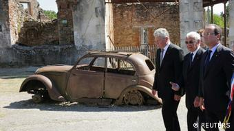 French President Francois Hollande (R), German President Joachim Gauck (L) and massacre survivor Robert Hebras walk in the streets of the French martyr village of Oradour-sur-Glane, near Limoges, September 4, 2013. Photo: REUTERS/Philippe Wojazer