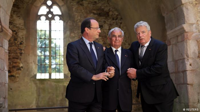French President Francois Hollande (L), German President Joachim Gauck (R) and massacre survivor Robert Hebras hold hands as they stand in the church of the French martyr village of Oradour-sur-Glane, near Limoges, September 4, 2013. Six hundred forty-two inhabitants of Oradour-sur-Glane, men, women and children, were massacred by soldiers of a German Waffen-SS Panzer division who also destroyed the entire village on June 10, 1944. A new village was built nearby after the war, but the remains of the original village has been maintained as a permanent World War II memorial and museum. REUTERS/Philippe Wojazer (FRANCE - Tags: POLITICS CONFLICT TPX IMAGES OF THE DAY)