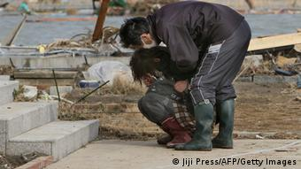 Two victims of the earthquake in front of their damaged home in the Japanese town of Watari on March 14, 2011. (Photo: JIJI PRESS/AFP/Getty Images)