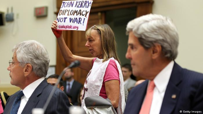 Medea Benjamin (C) of CodePink protests as U.S. Secretary of State John Kerry (R) and Defense Secretary Chuck Hagel testify during a hearing on Syria: (Photo by Alex Wong/Getty Images)