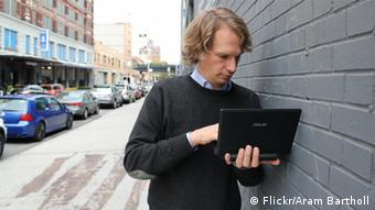 Artist Aram Bartholl leans against a brick wall with his laptop Photo: Flickr/Aram Bartholl
