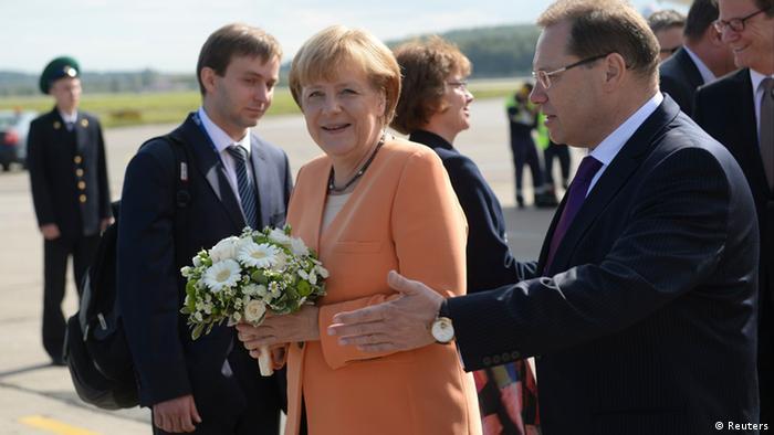 Blumen für die Kanzlerin: Merkel bei der Ankunft in St. Petersburg (Foto: Reuters)